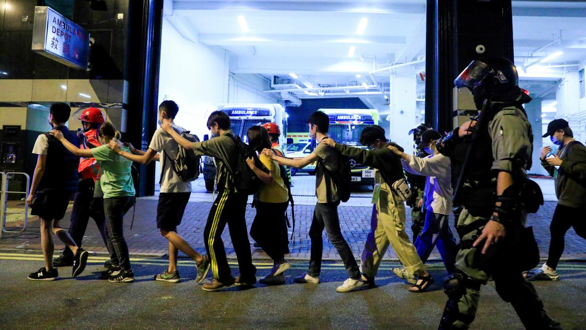 Protesters are escorted by police out of the campus of Hong Kong Polytechnic University during clashes with police in Hong Kong on Monday.