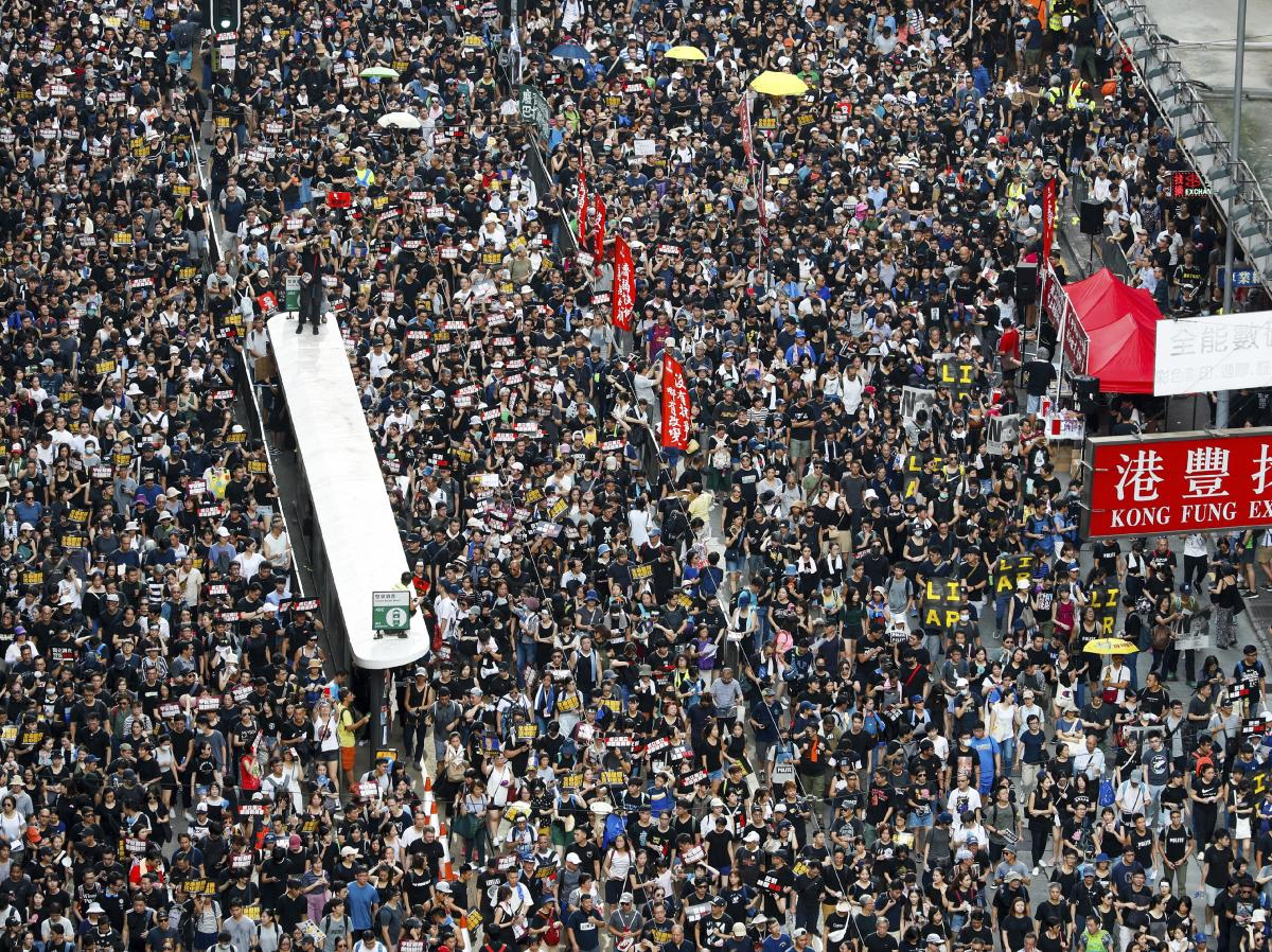 Protesters take part in a march on a street in Hong Kong on Sunday. Thousands of Hong Kong protesters marched from a public park to call for an independent investigation into police tactics.