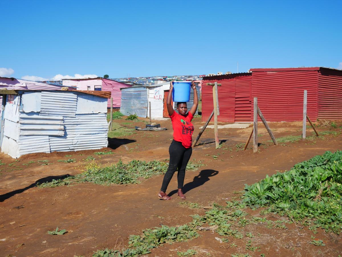 Annah Goba, 20, carries water to her shack in Azania, the name squatters gave to a section of private property they took over in Stellenbosch. Goba said the lack of running water was a challenge, but she couldn't afford to pay rent in crowded Kayamandi to