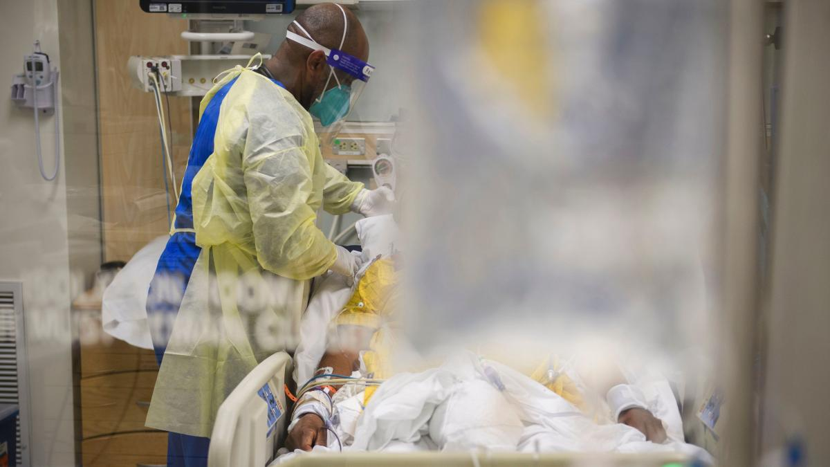 A hospital staff member attends to a patient in a COVID-19 intensive care unit on Jan. 6, 2021, at a hospital in Los Angeles.
