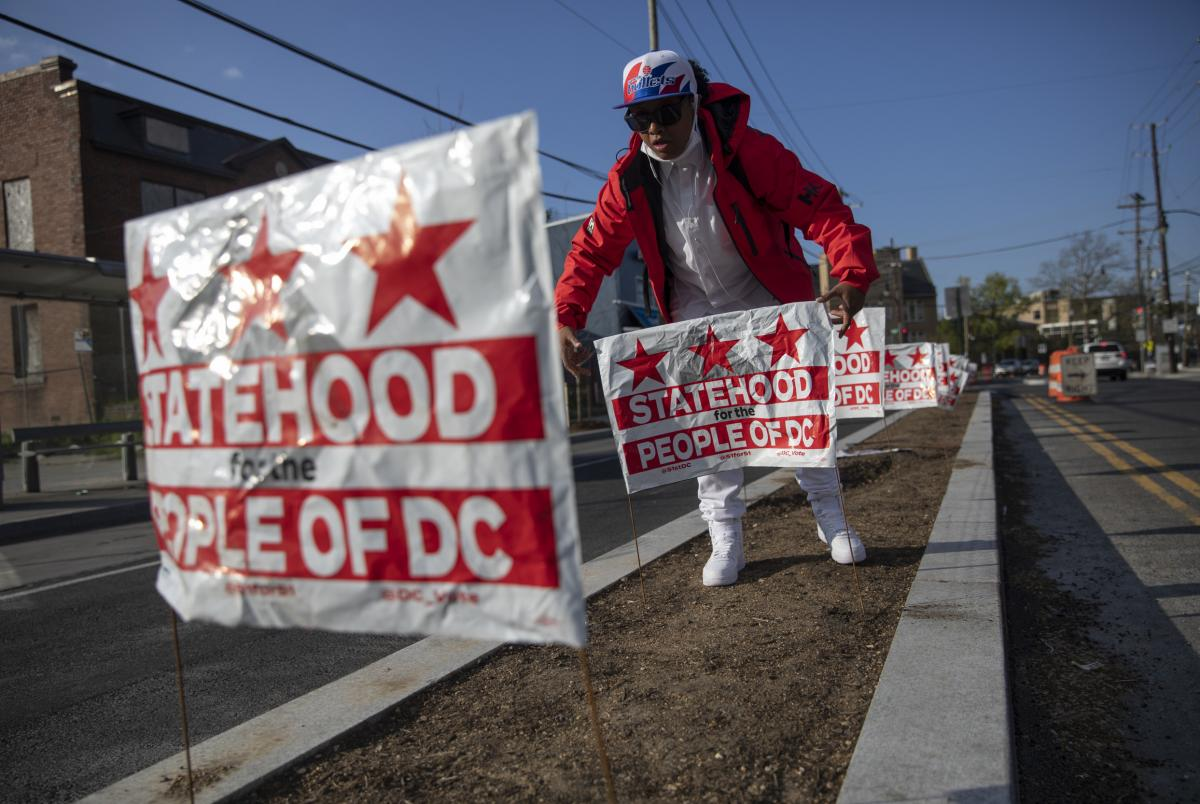 Jasmine Joyner places signs at Martin Luther King Jr. Ave & Malcolm X Ave SE in Washington, D.C.