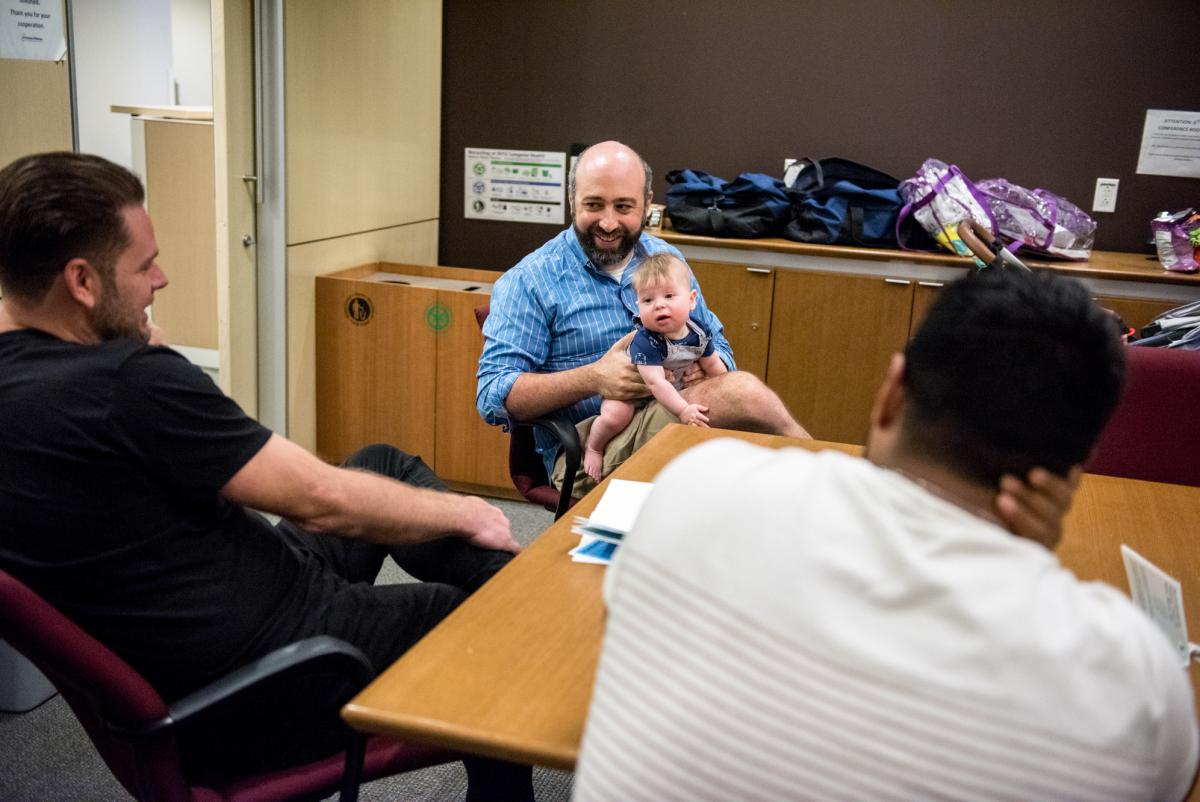 Guests of the class Jesse Applegate (center) and his son, Jacob, field questions from Saxon Eldridge (left), and Chris De Souza (right) about what to expect after the baby's born.