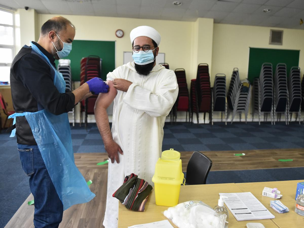 Mohammed Amir, the imam of the Stoke's City Central Mosque, receives a COVID-19 vaccination in February in Stoke, England. Imams across the United Kingdom are reassuring Muslims that the COVID-19 vaccine is permissible under Muslim law, as disinformation