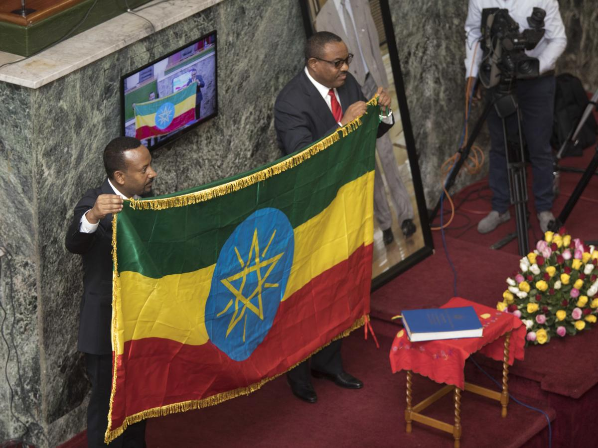 Abiy Ahmed (left) holds an Ethiopian flag with his predecessor, Hailemariam Desalegn, at the Ethiopian Parliament, following Ahmed's swearing-in ceremony as prime minister in April.