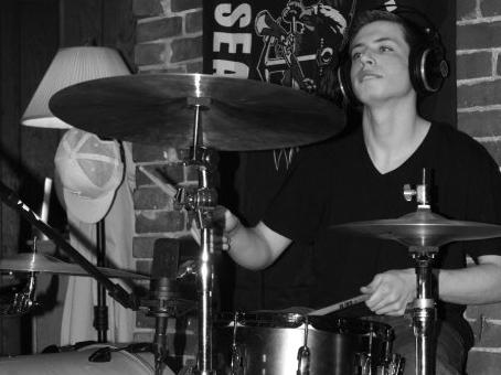 """Max at his drum kit. Playing the drums was Max's passion, his family says, as was """"creating original music, listening to jazz, rock, and blues, shooting pool, following the Red Sox and Patriots, playing fantasy football with his family, and enjoying card"""