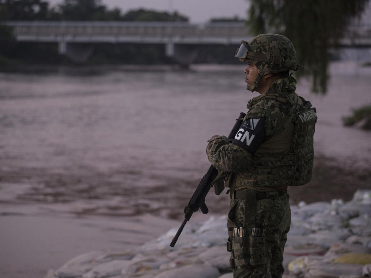 A member of Mexico's new National Guard watches over the Suchiate River to prevent illegal border crossings from Guatemala into Mexico's southern border in Ciudad Hidalgo, Chiapas state.