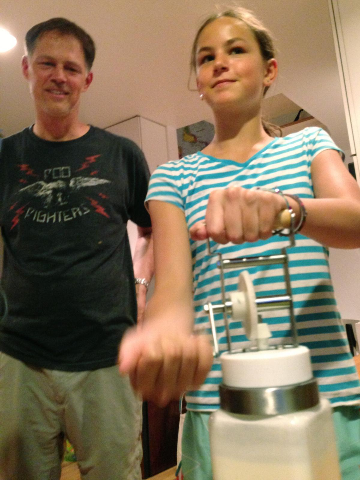 Riley Casagrande churns butter with her dad Jerry Casagrande.