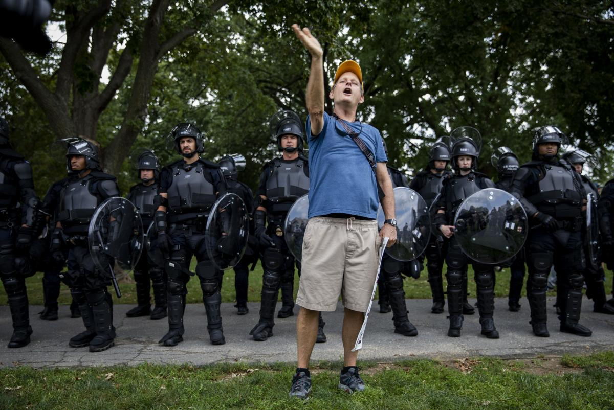Counterprotester Eric Lamar from Washington, D.C. stands in front of a line go Capitol Police.