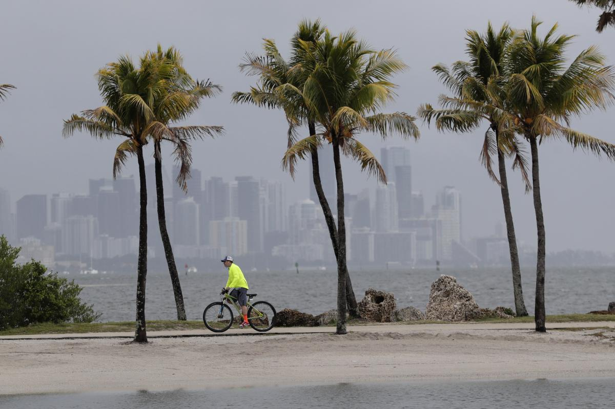 The Miami skyline is shrouded in clouds as a cyclist rides along Biscayne Bay. The National Oceanic and Atmospheric Administration has predicted an unusually active hurricane season this year, with more frequent and intense storms in the Atlantic Ocean. S
