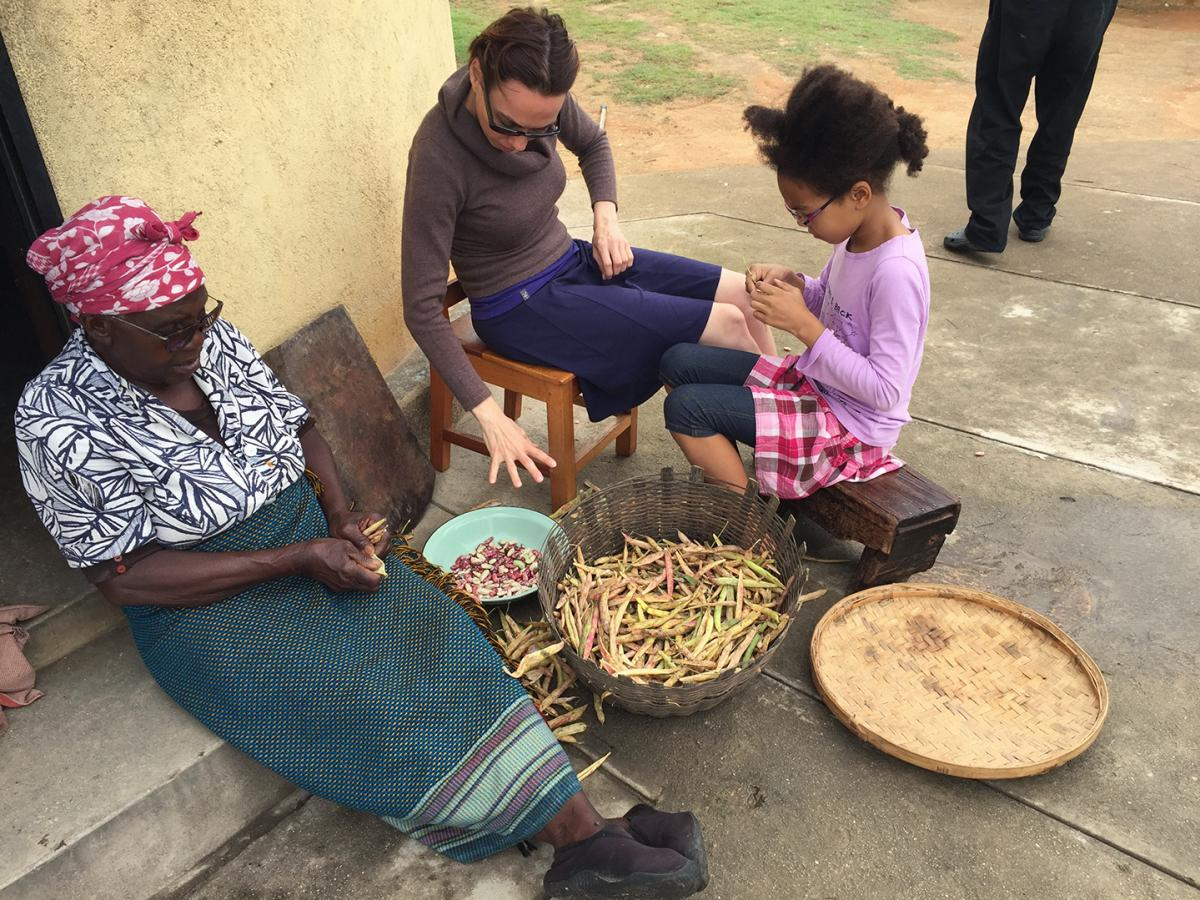 Gladys Mabaya (left) and her husband used income from their small farm to educate their 10 children. The author's wife, Krisztina Tihanyi, and their daughter, Izabella, help prepare beans for a meal during a Christmas visit to Zimbabwe.