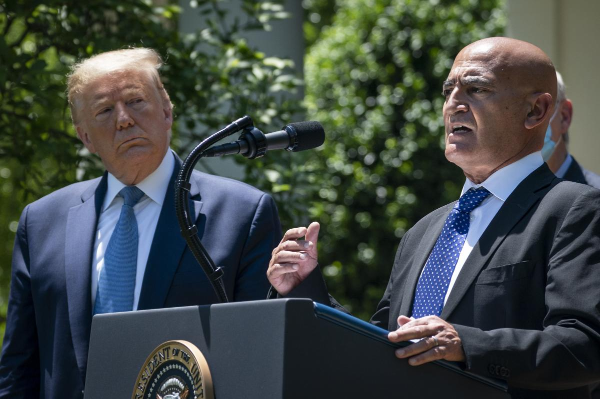 President Trump listens as Moncef Slaoui, the former head of GlaxoSmithKline's vaccines division, speaks about coronavirus vaccine development in May. Slaoui, an immigrant, is the chief adviser to Operation Warp Speed.