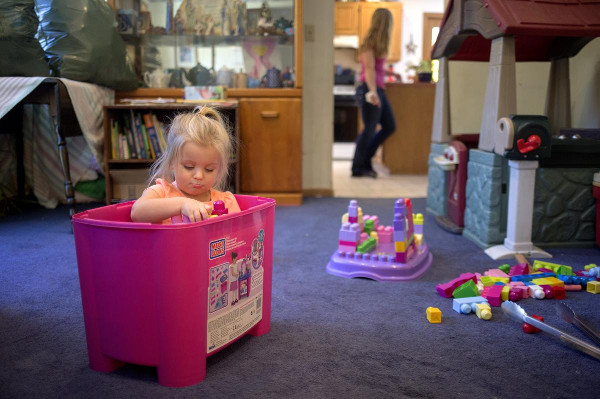 Audree, 2, plays while her mother, Samantha Watson, cleans the kitchen in 2016 in Maine. Watson, a single mother and nursing student, received benefits from the Temporary Assistance for Needy Families program.