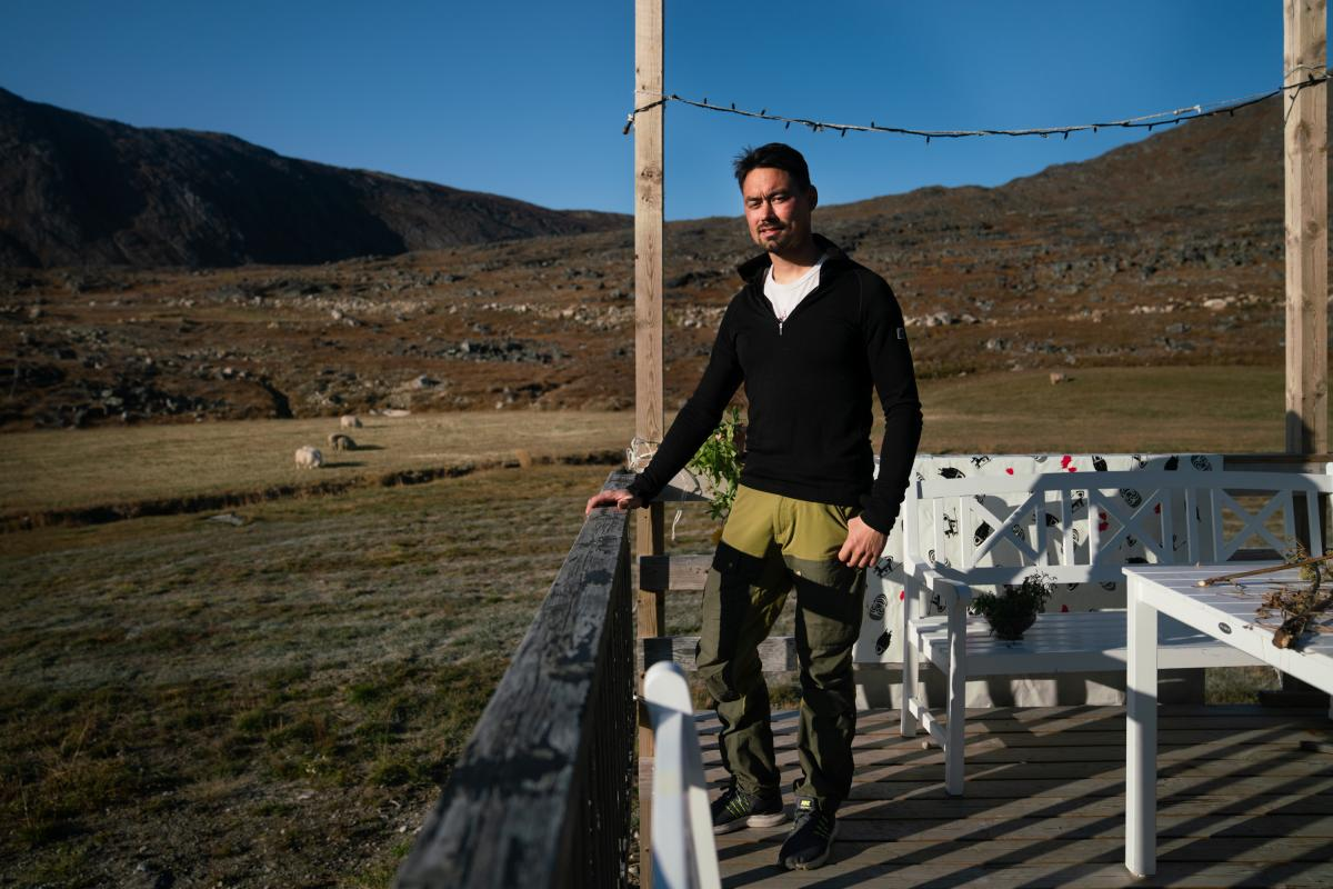 Kunuk Nielsen stands on the deck of his family's home. He's spent his entire life on the sheep farm.