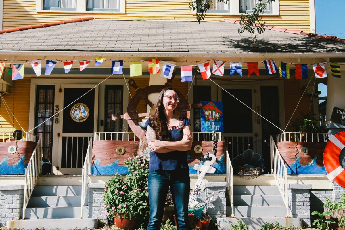 """Megan Boudreaux, founder of Krewe of House Floats, stands outside her own home and the 'USS House Float,' in Algiers Point. """"It's a little surreal how we got to this place,"""" Boudreaux said."""