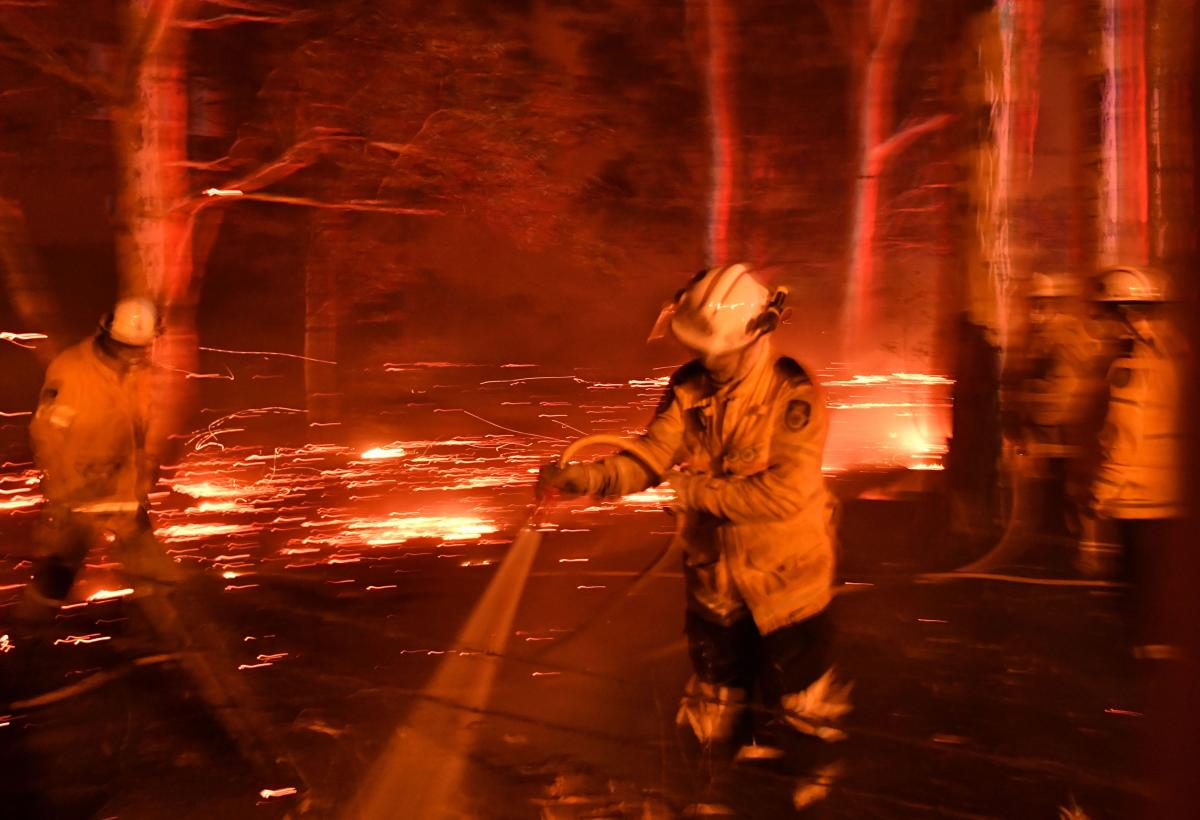 Firefighters hose down the area as they battle against bushfires around the town of Nowra in the Australian state of New South Wales on December 31, 2019.
