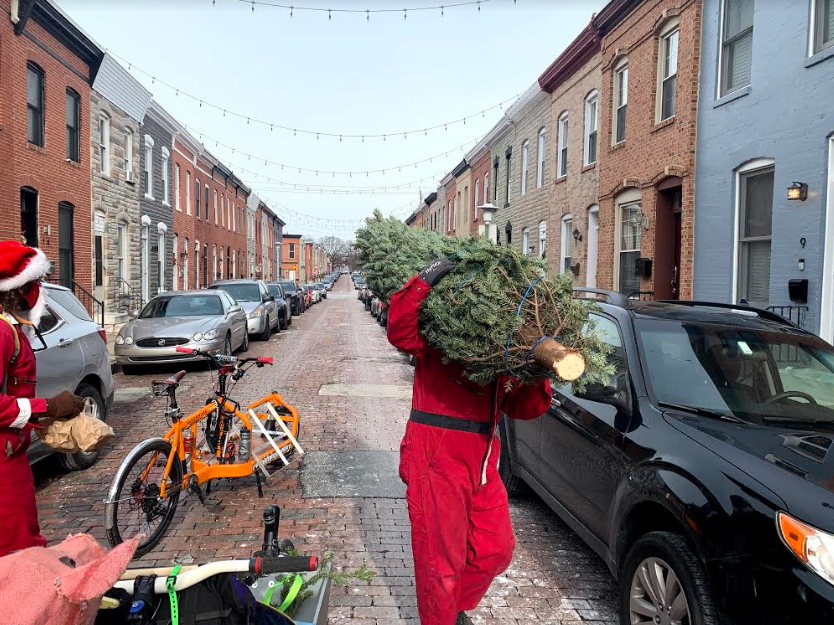 Mike Santoro lifts a tree off his cargo bike and into a row house.