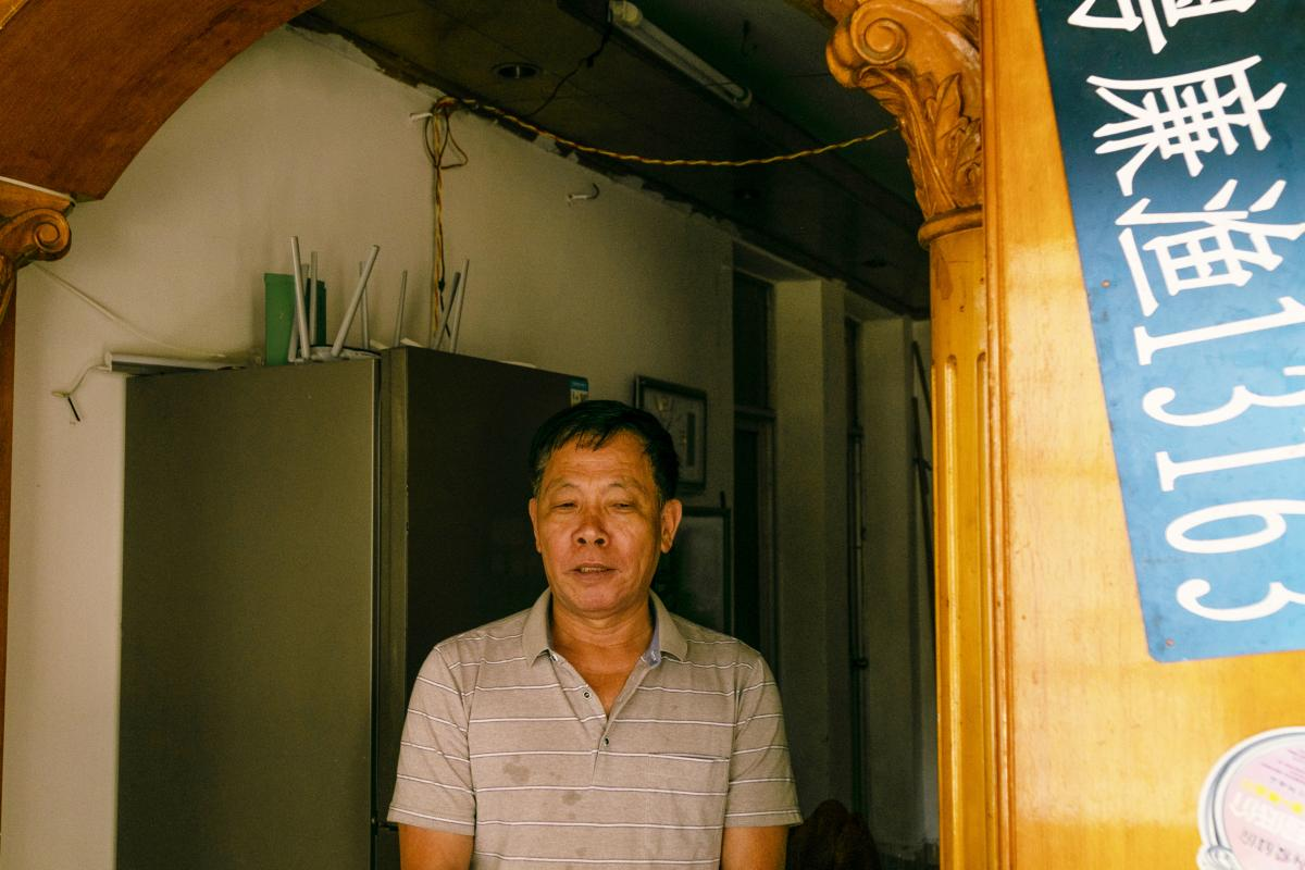"""Feng Daokun in the apartment he rents in Zhuhai, China, where he lives with his mother, wife and children. In his sister's last call to him, the day before she was killed, """"She specifically told me to ask our ancestors for protection so that she could get"""
