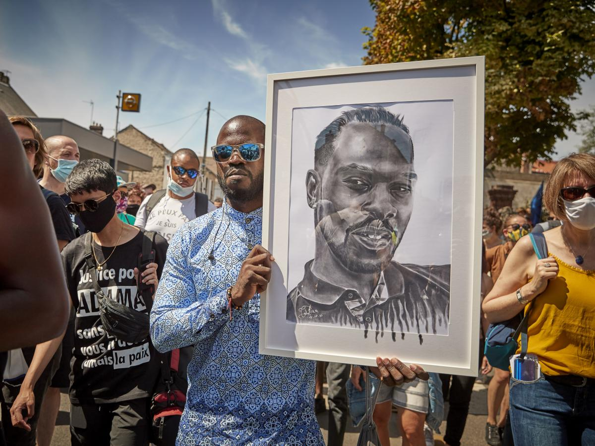 A protester holds a portrait of Adama Traoré during demonstrations to commemorate the fourth anniversary of his death, in Persan, France. Last week, judges in charge of investigating Traoré's case announced that various elements of the case would be ree