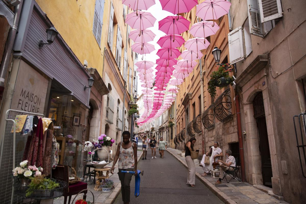 The historic center of Grasse was once home to perfume factories that have since moved out of the old town. Pink umbrellas are suspended above the streets every May through October, representing the Grasse May rose, which blooms only in May.