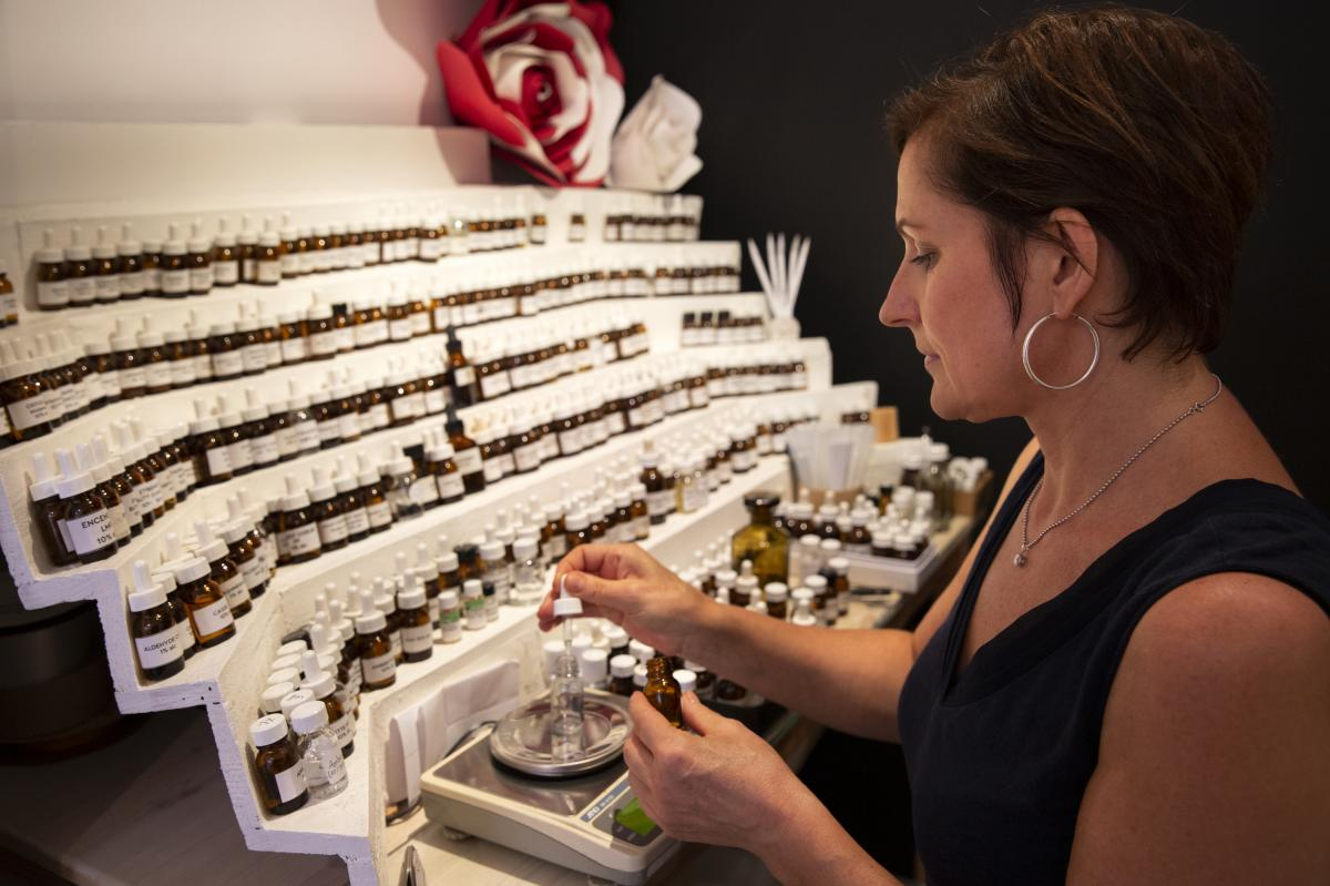 Jessica Buchanan, owner of the 1,000 Flowers shop in Grasse, creates perfumes at her perfumer's organ displaying hundreds of vials of scents.