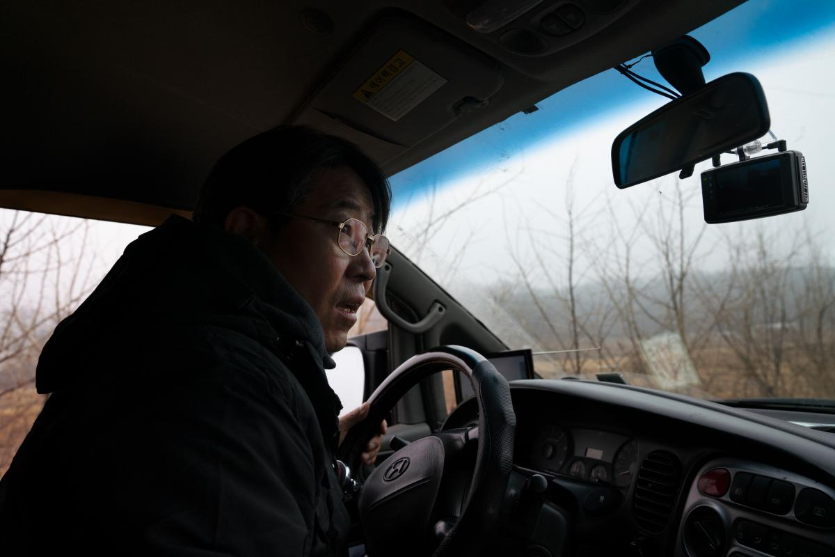 Kim Seung-ho drives through the CCZ looking for birds out his van window.