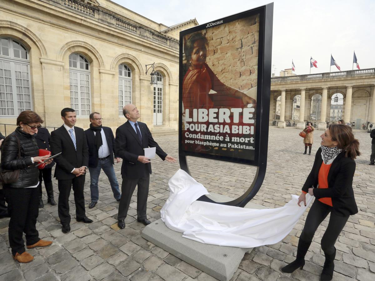 Asia Bibi's case has attracted international attention. In March Alain Juppe, near left, mayor of the French city of Bordeaux, unveiled a poster in the city hall courtyard in honor of Asia Bibi. A similar poster is in front of the city hall in Paris.