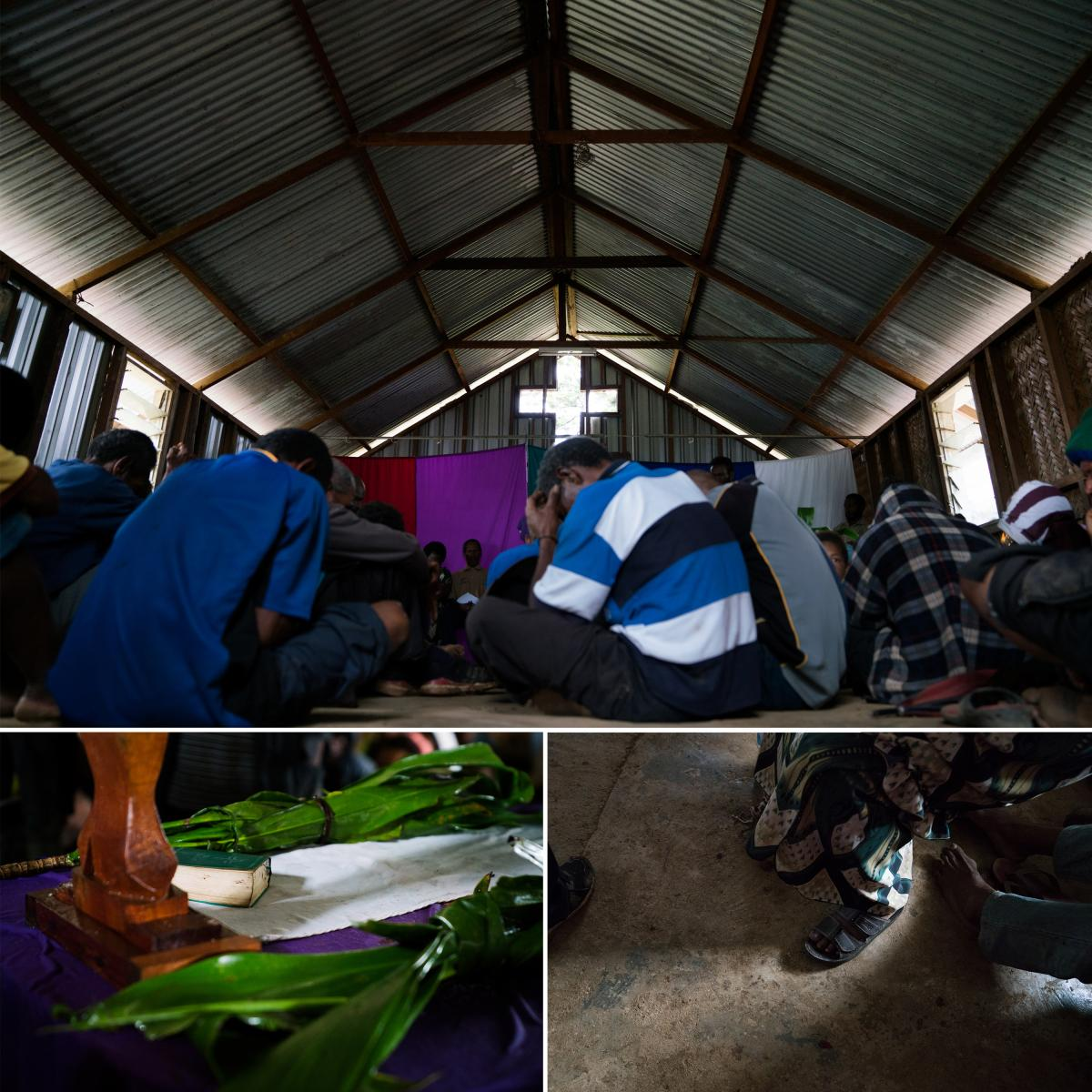 People bow their heads during a prayer at the reconciliation meeting in Henganofi. Leaves of the tanket plant and a Bible are set on a table in the center of the room.