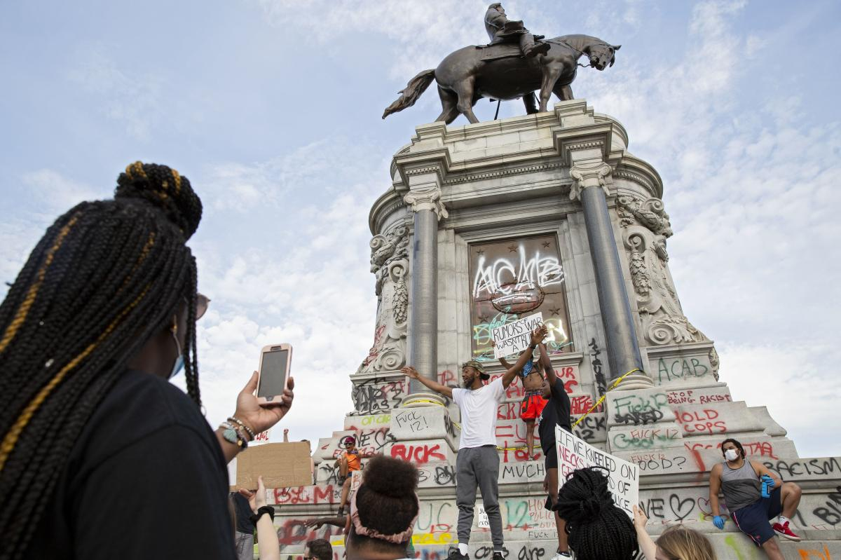 People gather around the Robert E. Lee statue on Monument Avenue in Richmond, Va., on June 4, amid continued protests over the death of George Floyd in police custody.