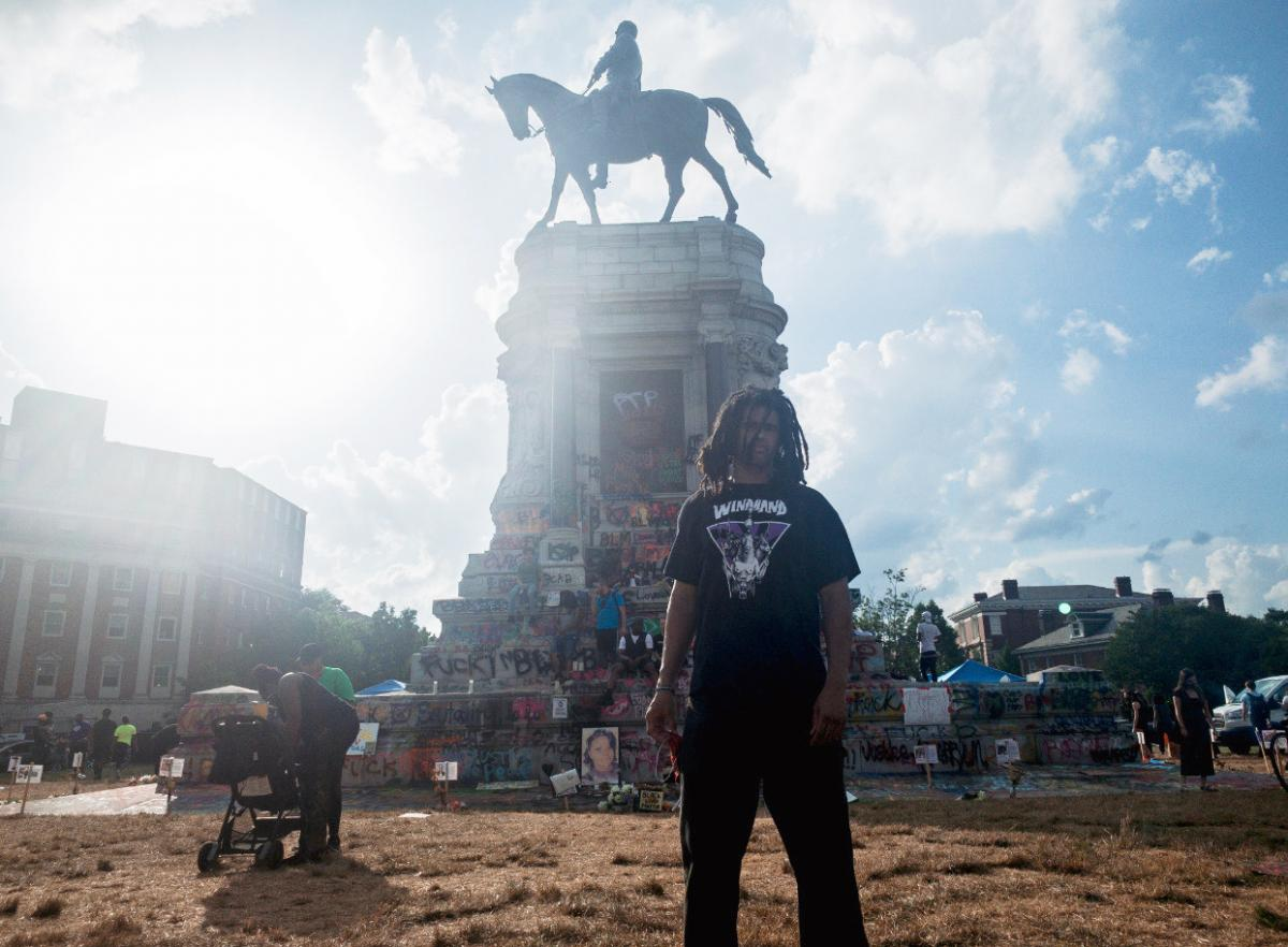 Richmond hip hop artist Rob Fields, known as Black Liq, poses in front of the Lee statue.