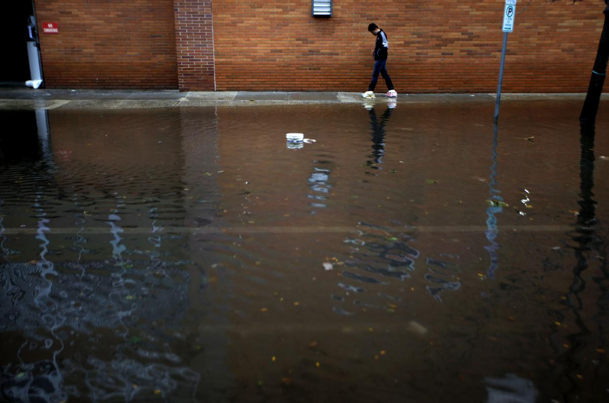 A resident traverses flooded streets as cleanup operations begin in Hoboken, N.J. The storm surge triggered deep flooding in low-lying neighborhoods.