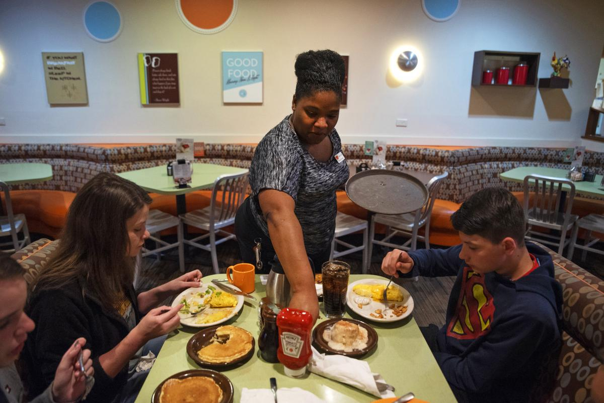 Tanisha Cortez waits on a table at a restaurant in Ames, Iowa. When the previous restaurant she worked for closed, Cortez applied to others and had job offers right away. Jobs are plentiful in Ames, a small city of more than 65,000 residents tucked amid f
