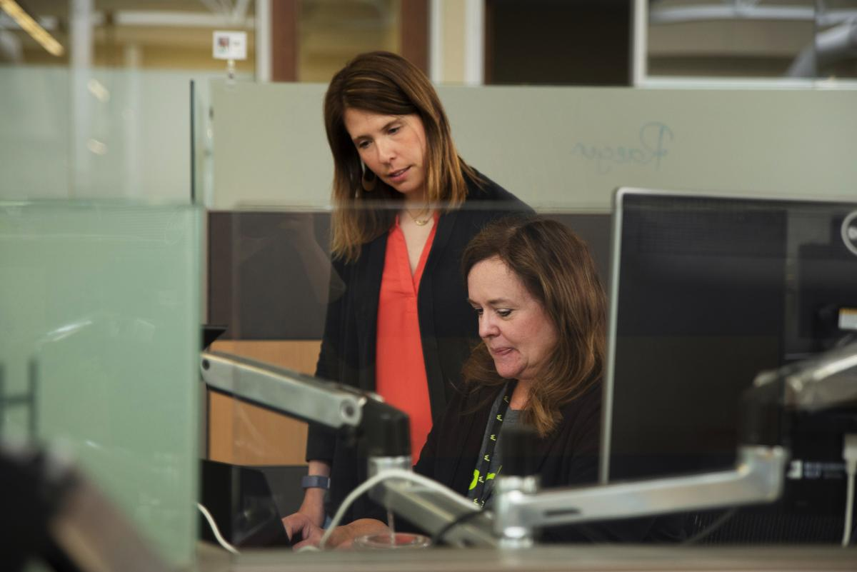 Forrester (left) looks over a training report with a colleague. Forrester says the company has to offer benefits like flex time and gourmet lunches to lure workers to the agricultural and college town of Ames.