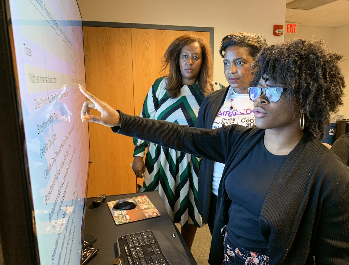 Cece Huddleston (right), an intern with the Congressional Black Caucus Foundation, reviews a dataset during a training session to make census outreach maps led by Jeanine Abrams McLean (center), Fair Count's vice president, and Menna Demessie, the foundat