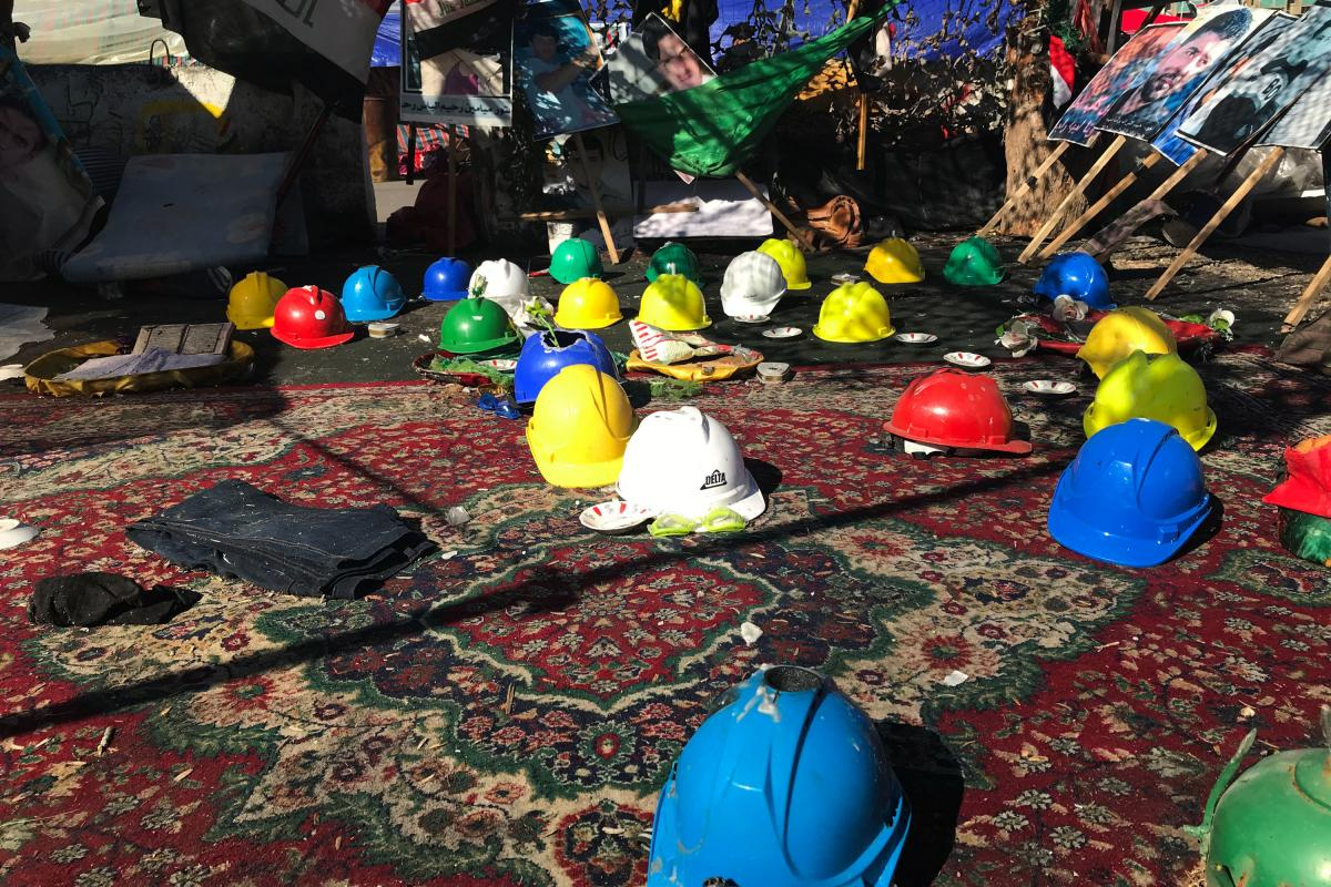 Protesters' helmets on display in Tahrir Square, some with holes where demonstrators were hit by tear gas canisters. The photos above are of protesters who were killed by security forces and militia gunmen.