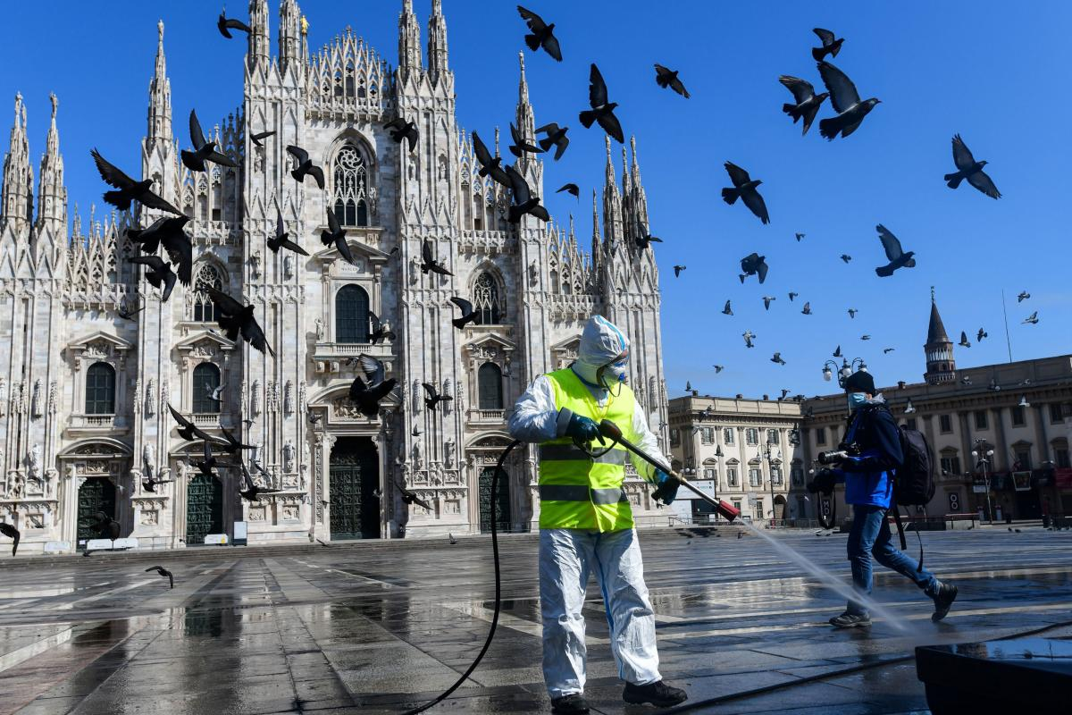 A man wearing protective gear sprays disinfectant on Piazza Duomo in Milan, in Lombardy, Italy, in March. Federico, who is from Lombardy, and his wife Liying, from Wuhan, pulled their younger child out of day care, and forbid both their children from goin