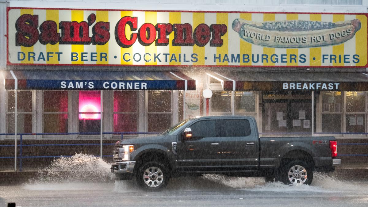 A truck passes the Sam's Corner restaurant in Garden City, S.C., on Monday during heavy rains from Hurricane Isaias. Now a tropical storm, Isaias is moving north-northwest along the U.S. Eastern Seaboard.