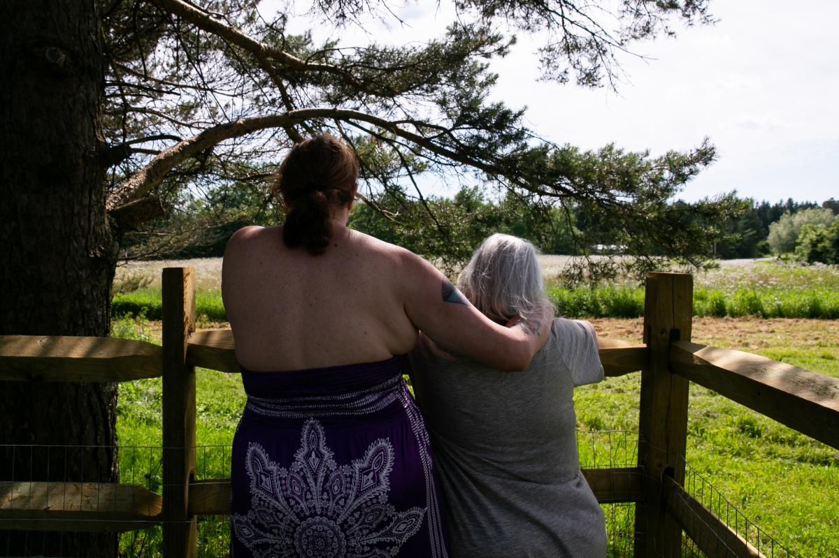 Gilbert and her wife, Alexandra, stand in their yard in upstate New York. Gilbert is suing Dell for, among other things, allegedly discriminating against her for her gender transition. The case is ongoing.