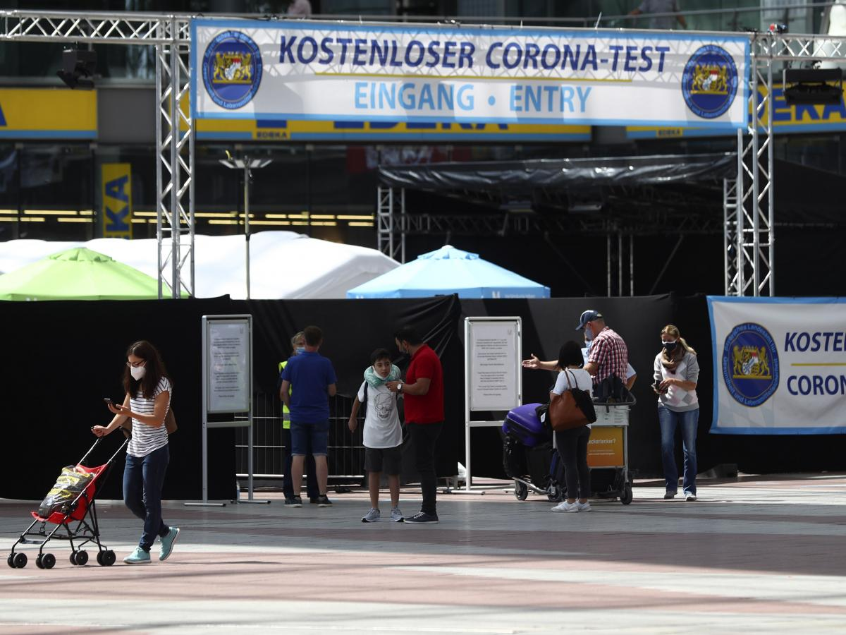 People pass a new coronavirus testing center last week at the airport in Munich. Passengers may be tested for the coronavirus for free.