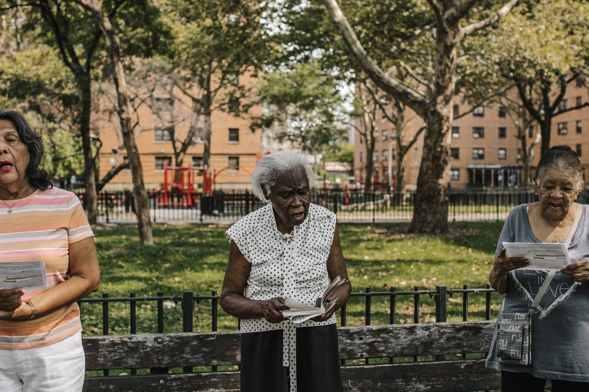 Margarita Barada (center) reads a passage during a service in a park across from the church of Our Lady Queen of Angels in New York City on Aug. 30.