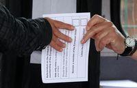A volunteer hands an unmarked ballot paper to a voter inside a bus being used as a polling station in Kingston-upon-Hull, northern England, on Thursday.
