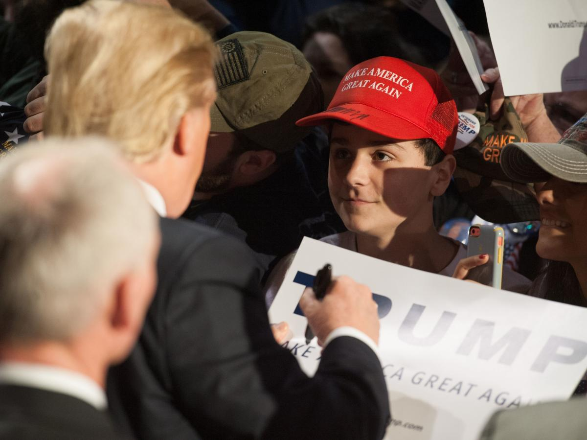 Donald Trump signs an autograph for a young man wearing a Make America Great Again hat during a rally in Millington, Tenn.