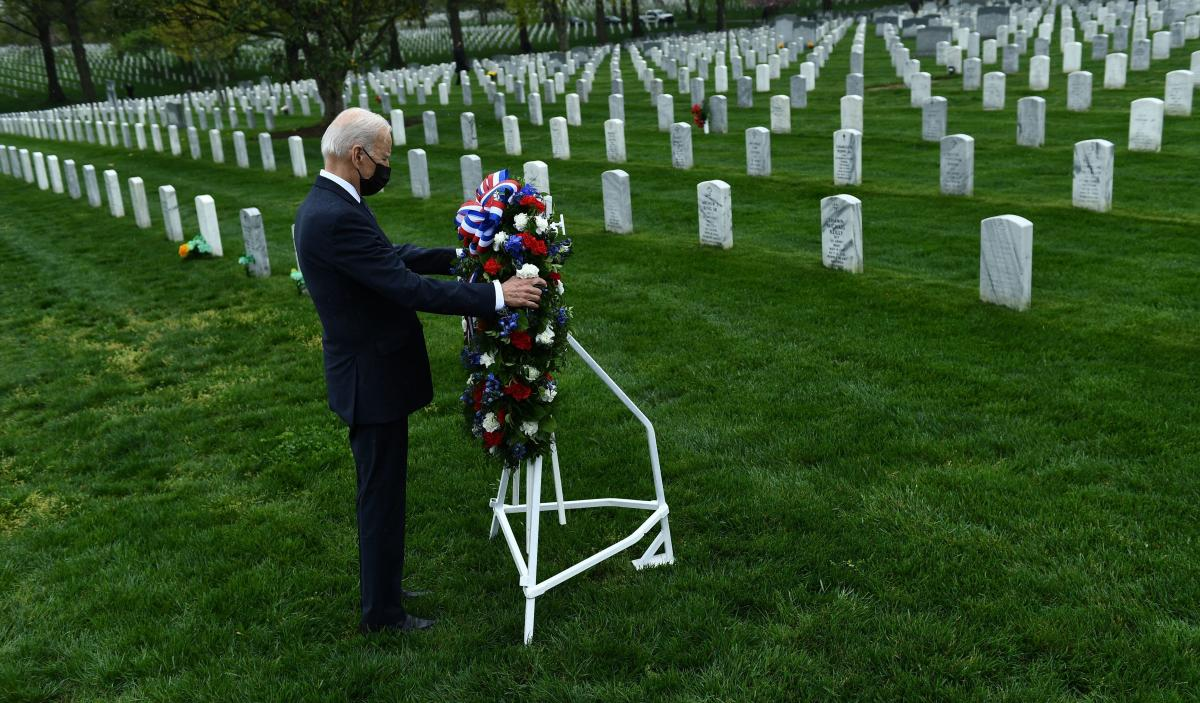 President Biden lays a wreath in Arlington National Cemetery to honor fallen veterans of the war in Afghanistan after speaking on Wednesday about his plans to withdraw U.S. forces from the country by Sept. 11, 2021.