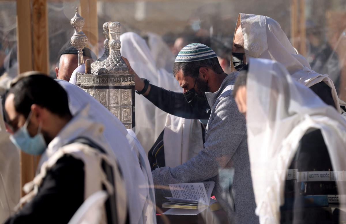 Jewish worshippers hold a Torah scroll as they recite the Priestly Blessing on the holiday of Passover in front of the Western Wall in Jerusalem on Monday.