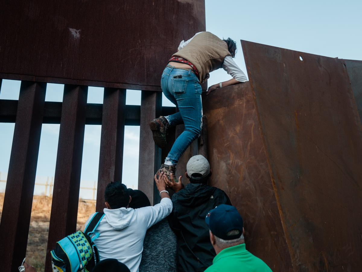 Drehsler's photo of a dozen migrants who decided to jump the border fence that divides the United States and Mexico in December. Drehsler and other journalists are facing increased scrutiny when they cross the border.