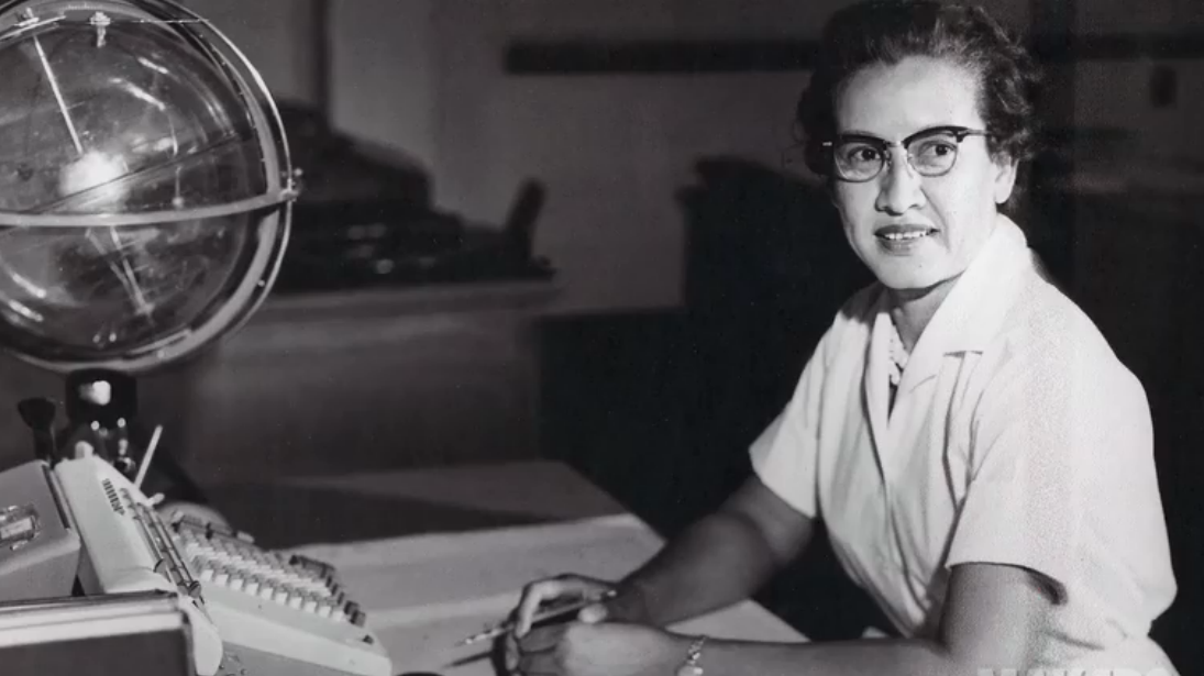 """Johnson at her desk at NASA Langley Research Center with a globe, or """"Celestial Training Device."""""""