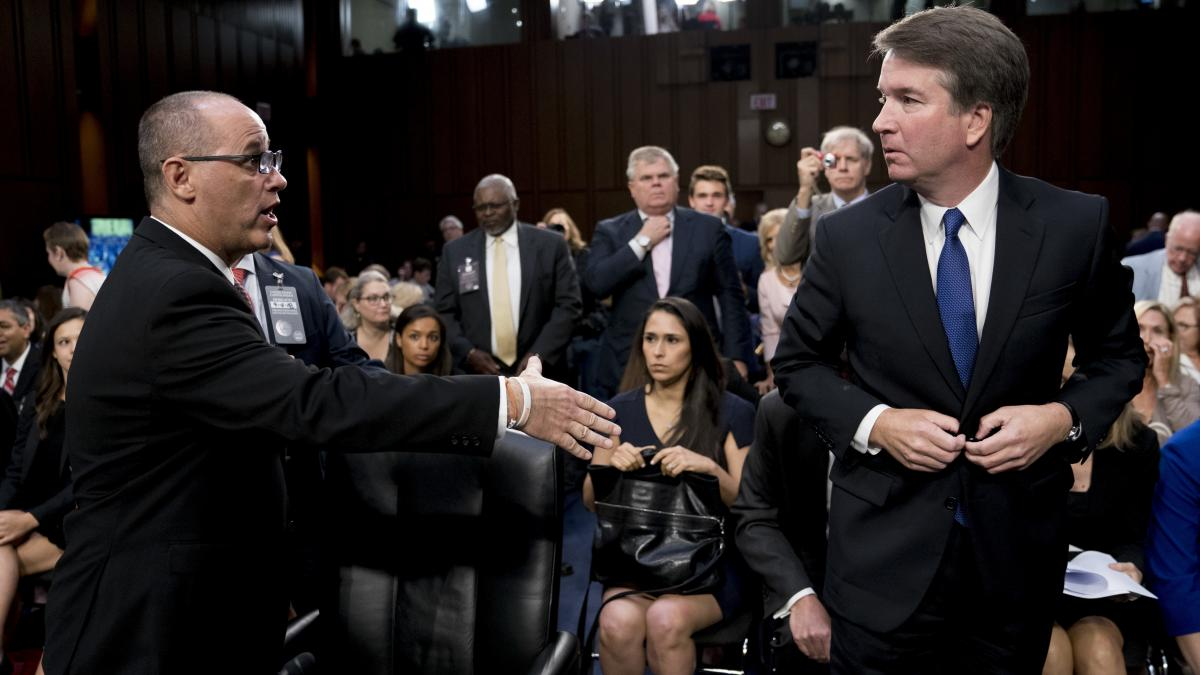 Fred Guttenberg (left), whose daughter, Jaime, was killed in the Marjory Stoneman Douglas High School shooting in Parkland, Fla., attempts to shake hands with Kavanaugh (right) as the nominee leaves for a lunch break while appearing before the Senate Judi