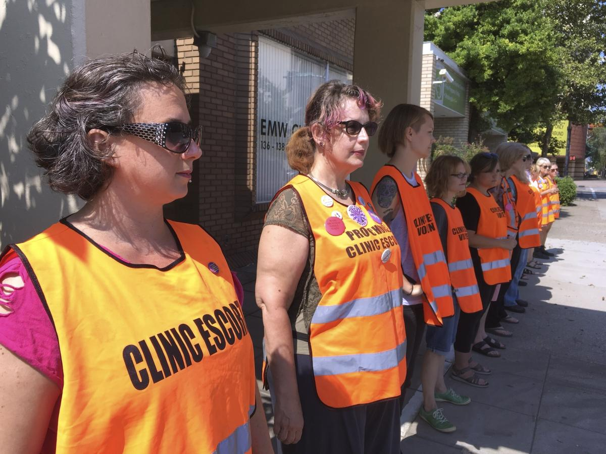 Volunteer escorts line up outside the EMW Women's Surgical Center in Louisville, Ky., ahead of a large anti-abortion-rights protest earlier this summer.