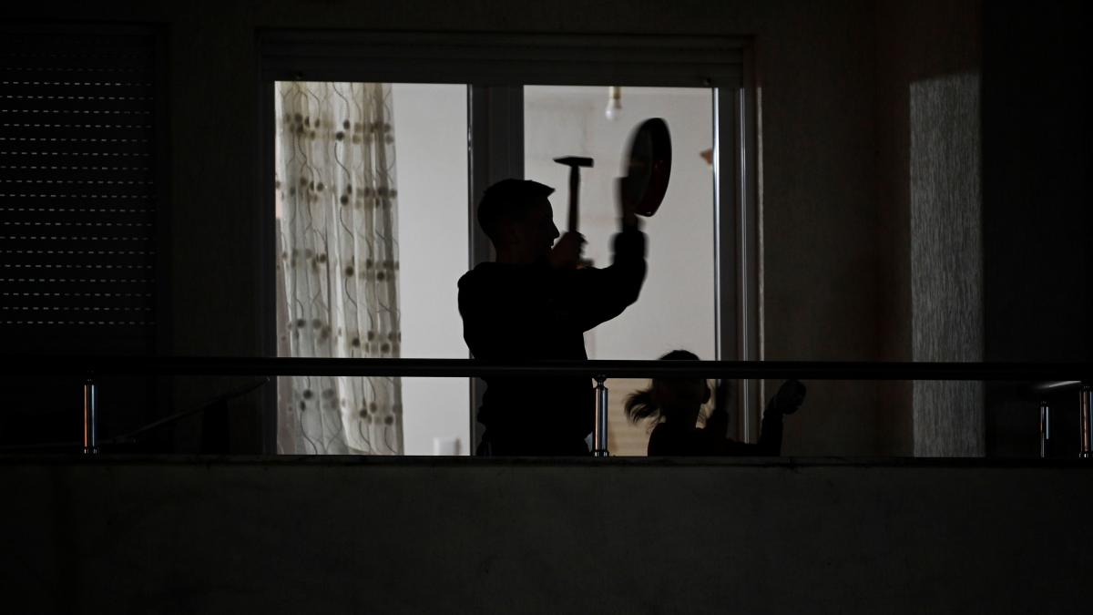 A man uses a hammer and a pan to make noise from his balcony last week in Pristina. The protest was intended to express frustration over the country's coronavirus response and the fight unfolding between its top politicians.