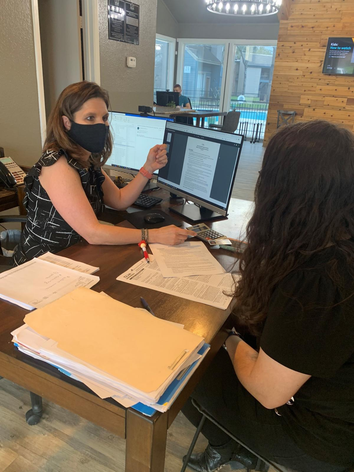 Stephanie Graves helps a tenant apply for rental assistance at the main office of one of her properties in Houston.