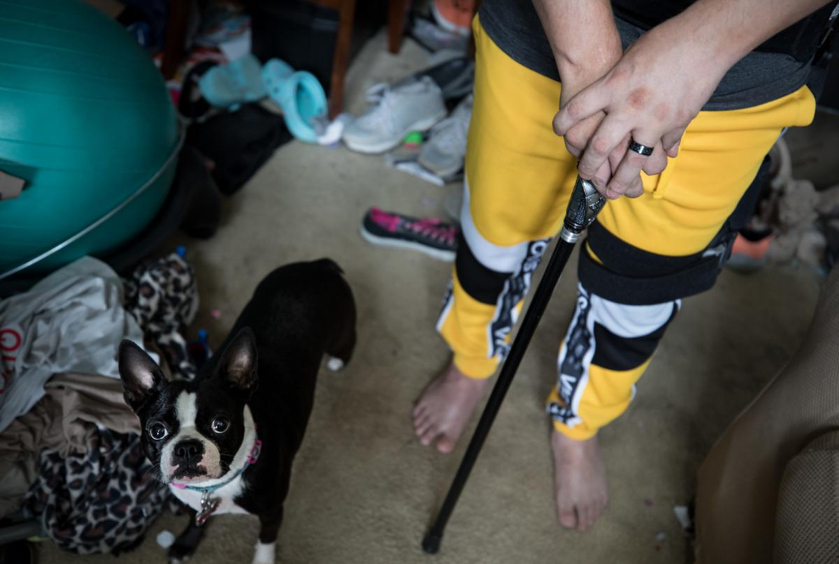 Marquette walks with the help of a cane and brace.